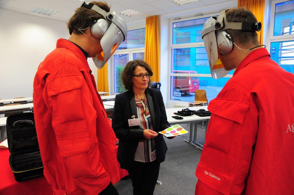 Frau Baltes vom Meyer-Hentschel Institut informiert zwei Teilnehmer über den Altersanzug AgeExplorer.